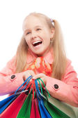 Young girl holds purchases and joyfully laughs — Stock Photo