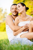 Young beautiful couple sits on grass — Stockfoto