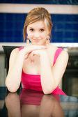 Fille en robe rouge assise à table — Photo