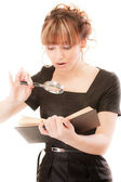 Beautiful girl reads book by means of magnifier — Stock Photo