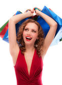 Rejoicing girl in red dress with purchases — Stock Photo