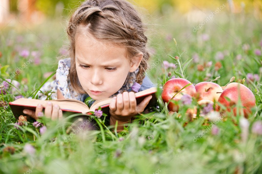Beautiful little girl with basket of apples reads book, lying on green lawn. — Stock Photo #3762954