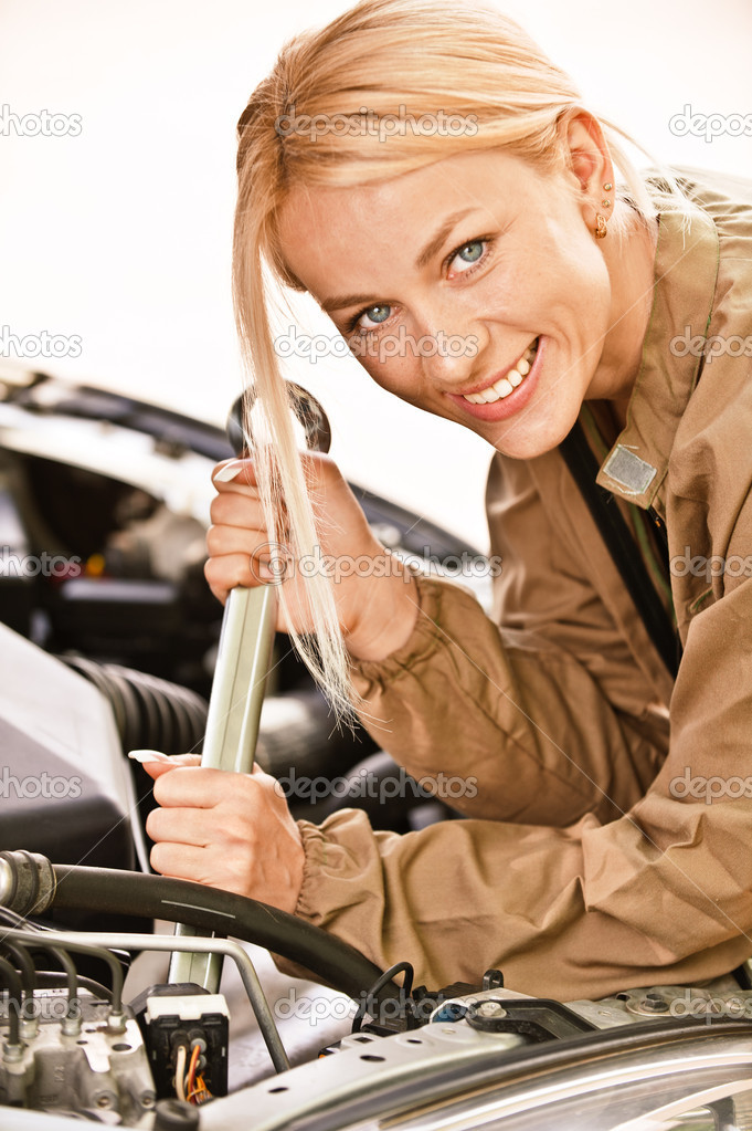 Woman car mechanician repairs engine of car and smiles.  Stock Photo #3763091