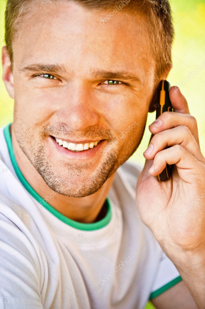 Young man smiles and speaks on phone, close up. — Stock Photo #3763211