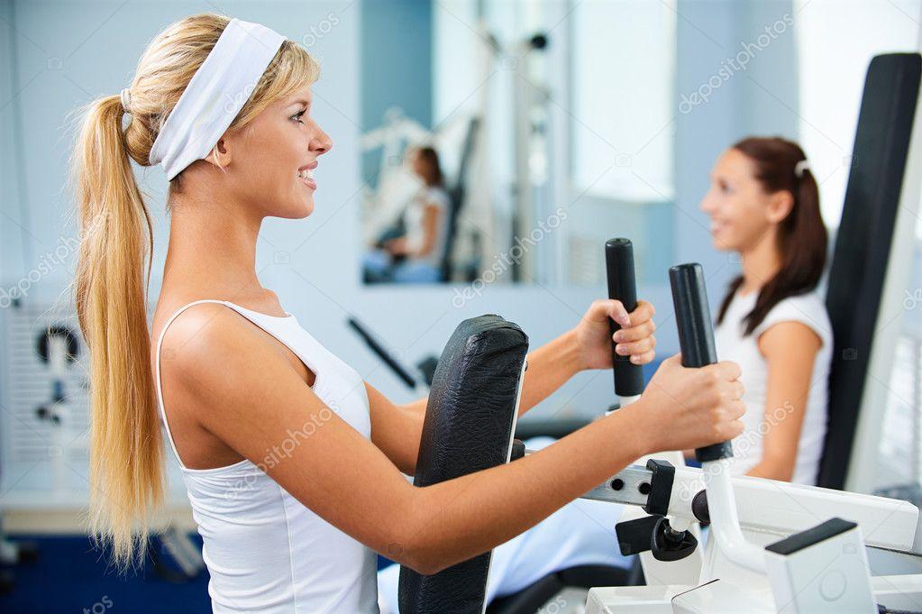 两个女孩在各种机器上健身房锻炼的肖像