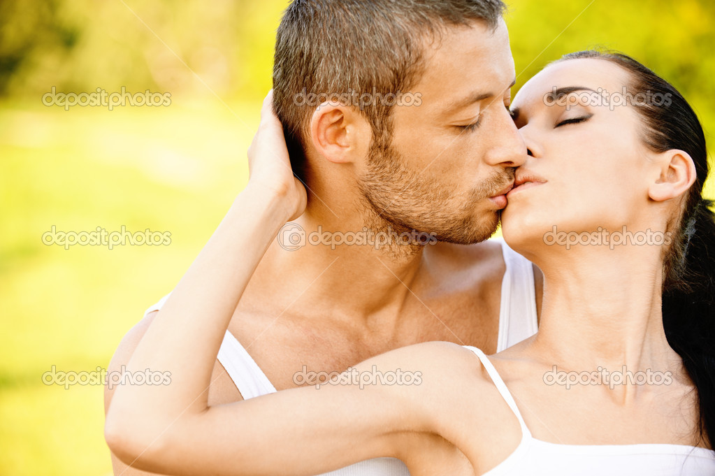 Young beautiful pair kisses against summer garden. — Stock Photo #3764812
