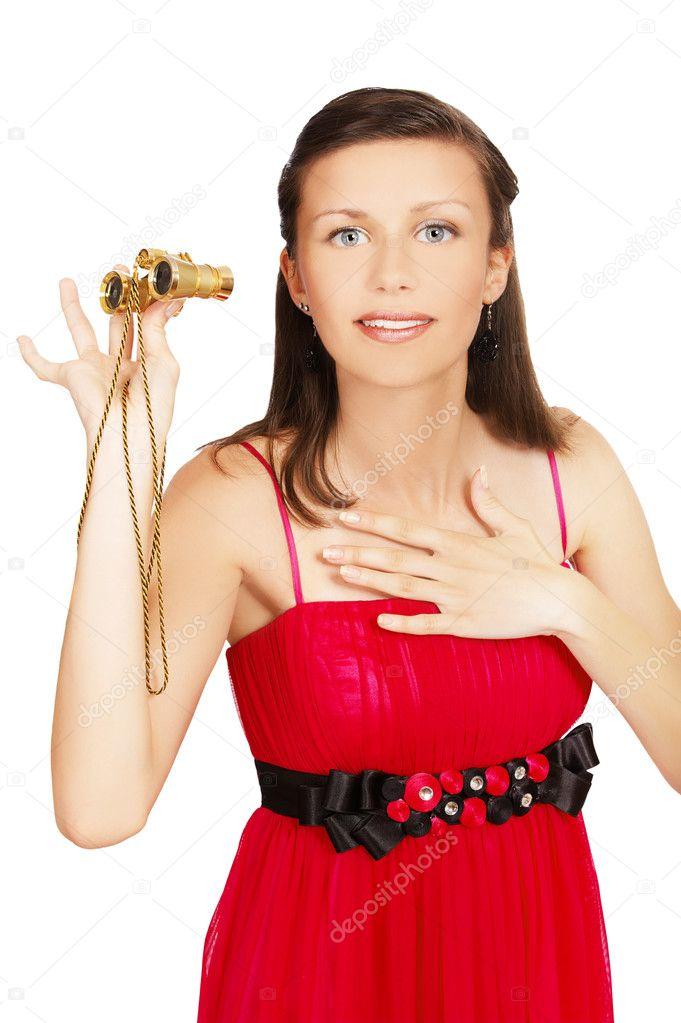 Portrait of amazed brunette in red dress with theatrcial binocular