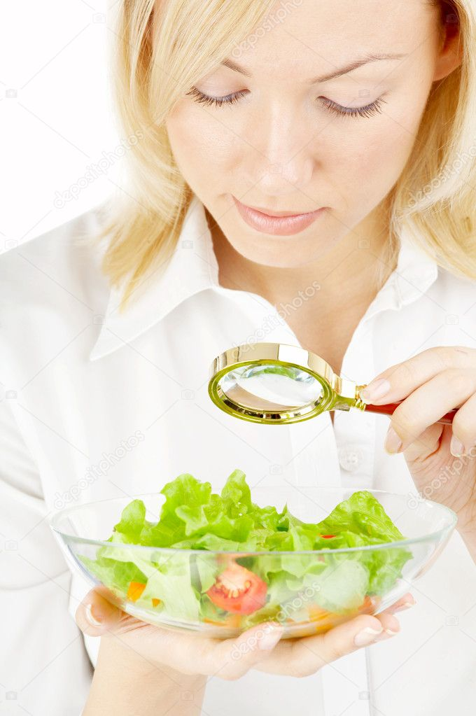 The blonde examining in a magnifier a plate with salad — Stock fotografie #2909900