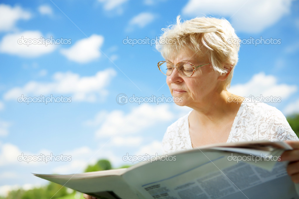 The elderly lady with the newspaper against the sky — Stock Photo #2910046