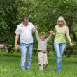 Family walking outdoors holding hands — Stock Photo