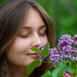 Teenage girl sniffing lilacs — Stock Photo