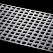 Punched metal isolated on black - Stock Photo