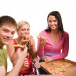 图库照片: Friends having fun and eating pizza