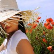 Young beautiful woman in poppy flowers - Stock Photo