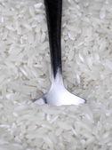 Rice background and teaspoon — Stock Photo