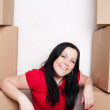 Woman sitting with cartons and moving in — Stock Photo #3098564