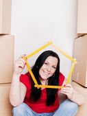 Woman with carton holding measuring tape — Stock Photo