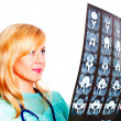 Female doctor examining x-ray picture over white - Stock Photo
