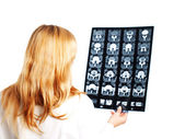 Female doctor examining x-ray picture over white — Stock Photo
