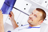 Male doctor holding xray in office — Stockfoto