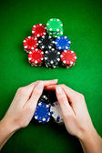 Female hands rakes up stack of gambling chips — Stock Photo