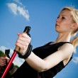 Nordic Walking - Young woman is hiking against blue sky. - Stock Photo