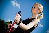 Nordic walking - młoda kobieta jest turystyka przeciw błękitne niebo. — Zdjęcie stockowe
