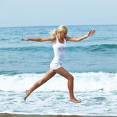 ビーチで跳んで幸せな若い女性 — ストック写真