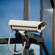 Security camera attached on business building with reflections — Stock Photo #3764197