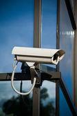 Cámara de seguridad atado en edificio con reflejos del negocio — Foto de Stock