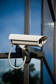 Security camera attached on business building with reflections — Stock Photo