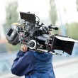 Camera operator carrying equipment - Stock Photo