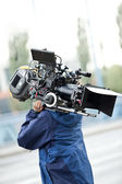 Camera operator carrying equipment — Stock Photo