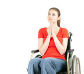 Praying young woman on wheelchair — Stock Photo