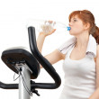 Drinking water woman on stationary bicycle — Stock Photo