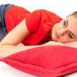 Royalty-Free Stock Photo: Young woman lying on the red pillow