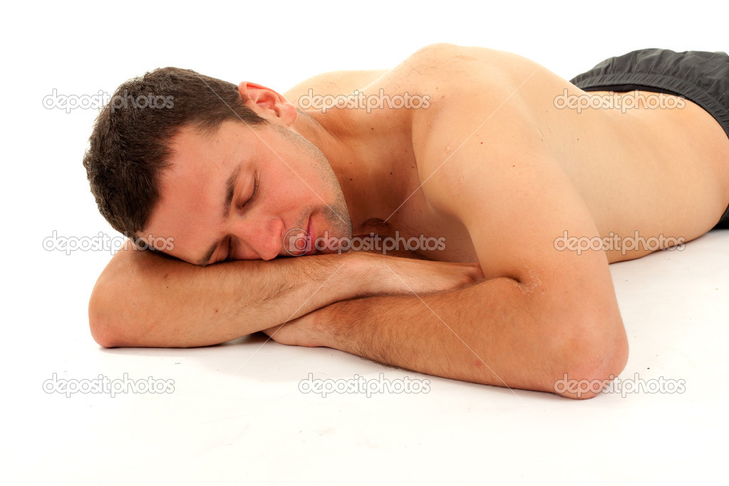 Nude young man sleeping on the floor with leaning on hands head