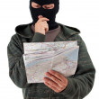 Thief in balaclava reading map - Stock Photo