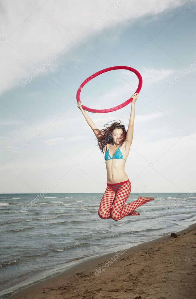 Active lady at the beach jumping with red hula hoop. Vertical photo  Stock Photo #2727856