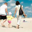 Family walking on the beach - Stock Photo