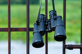 Binoculars hanging on metal grating — Stock Photo