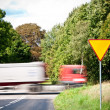 Stock Photo: Yield sign near crossroad and rushing truck