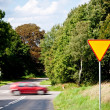 Yield sign near crossroad and rushing car — Stock Photo