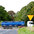 Yield sign near crossroad and rushing truck — Stock Photo