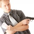 Young poker player with gun — Stock Photo