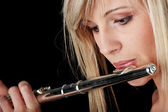 Portrait of a woman playing transverse flute — Stock Photo