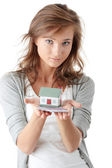 Woman holding euros bills and house model — Stock Photo