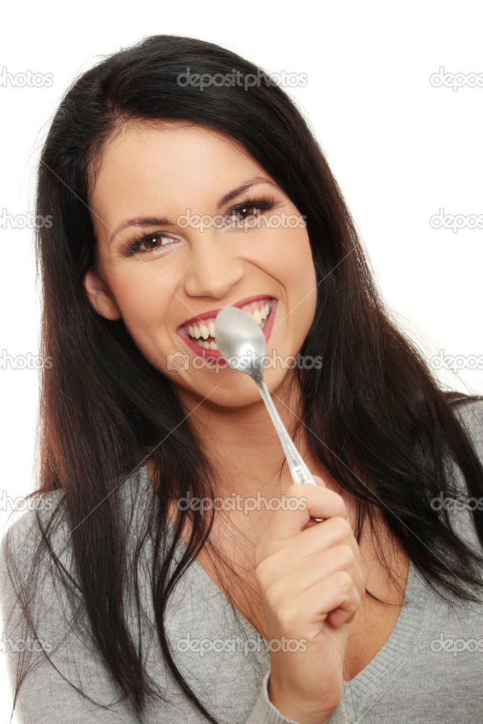 Portrait of young smiling woman with spoon in her mouth and (pleasure from eating), isolated on white  — Stock Photo #3858653