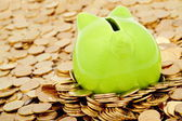 Green piggy bank and sea of gold money — Stock Photo