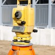 Yellow theodolite on a construction site - Stock Photo